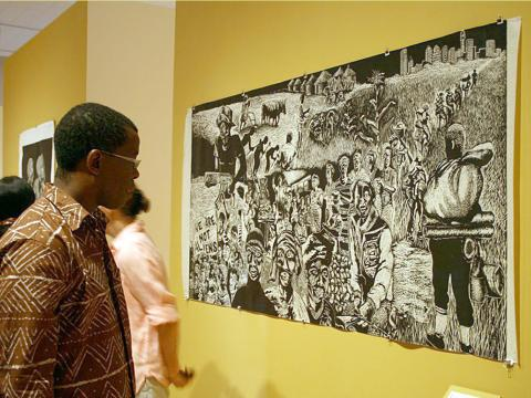 African American man studying artwork at Art Gallery