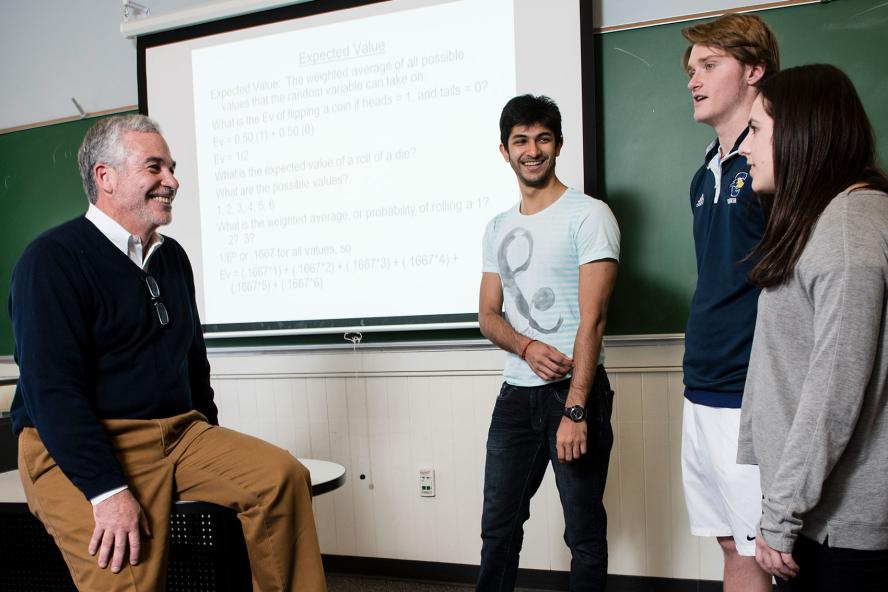 Chris Manos, Lecturer in Economics, with three students