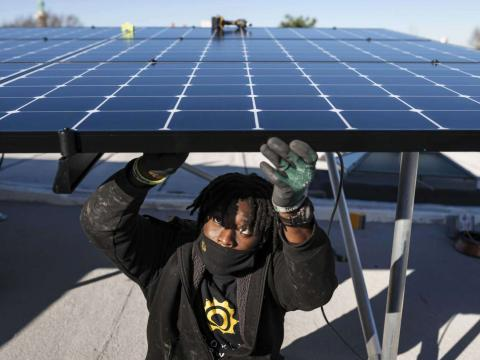 Keiron Clarke, a worker for Brooklyn SolarWorks, installs solar panels at a home in Brooklyn on Dec. 3, 2020. The firm, which serves New York City, buys solar panels through buyer collectives to get lower prices. (Karsten Moran/The New York Times)