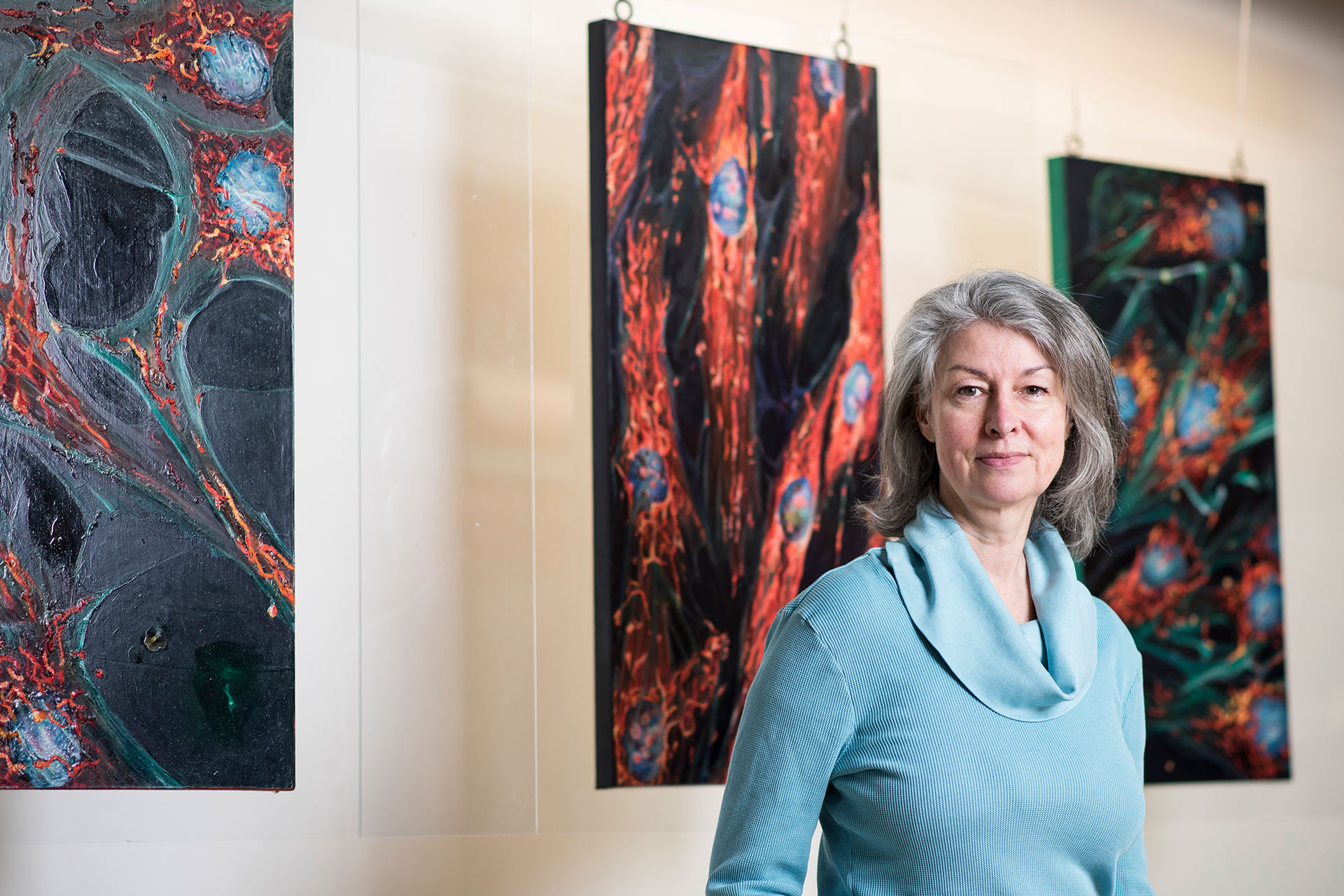 Artist Lynda Cutrell with some of her work at the CLIC Building at Tufts University