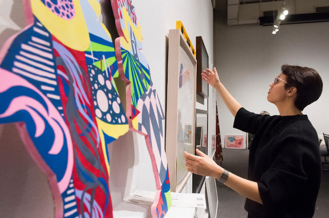 Monica Manoski oversees installation for the annual SMFA art sale, a fundraising event for financial aid at the School of the Museum of Fine Arts at Tufts.