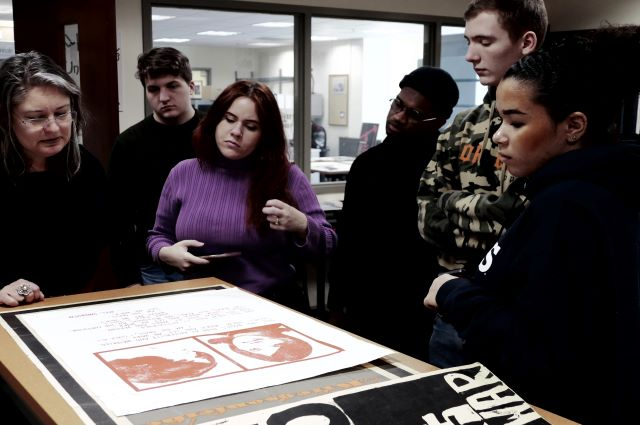 Chantal Zakari, left, and her students visited the Tufts archives in January for a close look at protest posters.