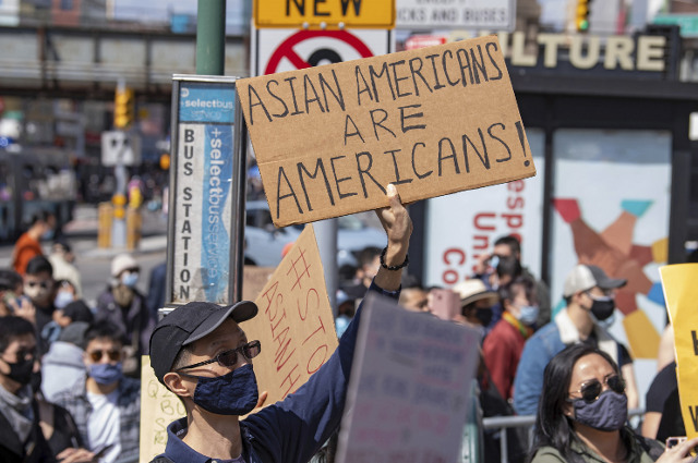 A man holds a sign at a March 27 rally in New York